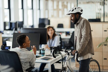 Businessman With Bicycle Talking To Businesswomen In Office
