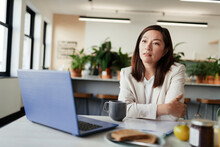 Thoughtful Businesswoman Working At Laptop In Office