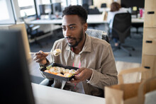 Businessman Eating Sushi Takeout Lunch At Computer In Office