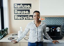 Portrait Confident Businesswoman At Recycling Bins In Office Kitchen