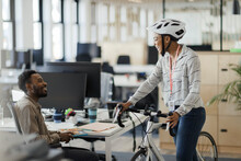 Businesswoman With Bicycle Talking To Businessman In Office