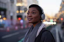 Beautiful Young Woman In Headphones On City Street