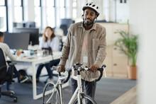 Businessman Walking Bicycle In Office
