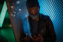 Young Woman In Face Mask Using Smart Phone In Blue Light