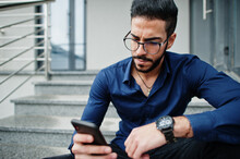 Middle Eastern Entrepreneur Wear Blue Shirt, Eyeglasses Against Office Building Sitting On Stairs And Look At Mobile Phone.
