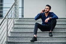 Middle Eastern Entrepreneur Wear Blue Shirt, Eyeglasses Against Office Building Sitting On Stairs And Speak By Telephone.