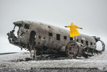 A Man In A Yellow Raincoat Near The Crashed DC-3 Plane That Crashed In Sólheimasandur. Landmarks Of Iceland. Iceland, December 2020