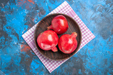 Overhead View Of A Brown Pot With Fresh Pomegranates On Pink Stripped Towel On Isolated Blue Background