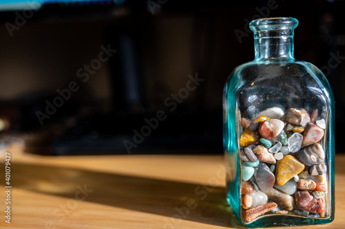 Fototapeta Glass bottle half full of rounded pebbles and rocks obraz