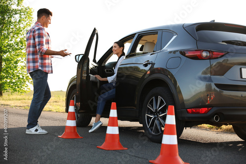 Tablou Canvas Instructor near car and his student outdoors. Driving school exam