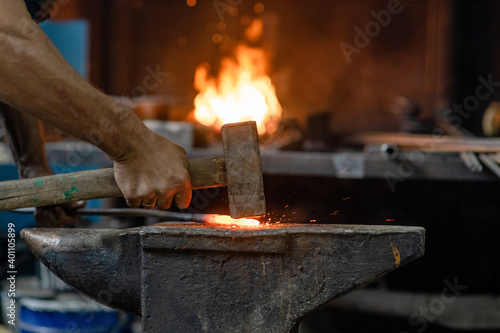 Tela Blacksmith working metal with hammer on the anvil in rustic forge