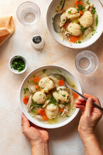 Female Eating Chicken And Dumpling Soup From A Bowl