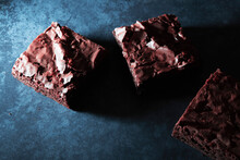 Chocolate Brownies On A Dark Blue Background.
