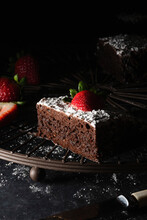 Chocolate Brownie With Dusted Icing Sugar And A Strawberry.