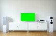 Widescreen modern green screen TV for text and video on a chrome stand against a white wall.