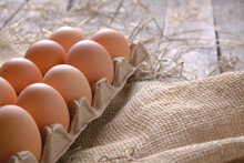 Chicken Eggs In A Tray In A Chicken Coop On A Sackcloth With Hay.