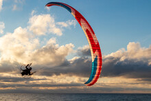 Paraglider Flying In The Cloudy Sky. Paragliding Sport Concept.