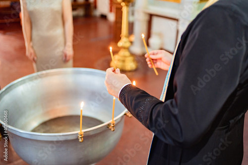 Tablou Canvas a priest holds candles in hands near the baptismal font.