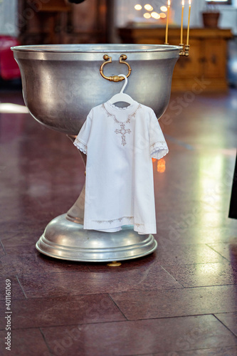 Foto a white children christening shirt hangs on the font in the Church