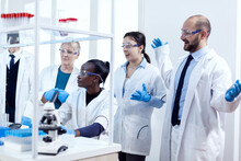 Group Of Scientists With Diverse Race Working To Find A Cure Vor Virus During Pandemic. Black Healthcare Researcher In Biochemistry Laboratory Wearing Sterile Equipment.