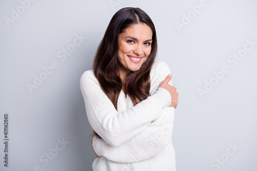 Fototapeta Portrait of attractive cheerful brown-haired girl embracing herself soft clothes