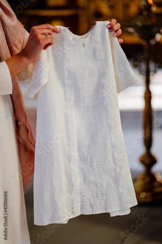 Canvas a white children christening shirt in the Church.