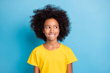Photo Of Dreamy Cute Little Afro American Girl Look Empty Space Wear Yellow T-shirt Think Bite Lip Isolated On Blue Color Background