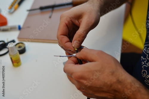 Fototapety, obrazy: Close-up of male hands connecting wires.