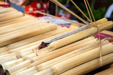 Street Food Market In Asia. A Man Sells Rice In Bamboo Stalks