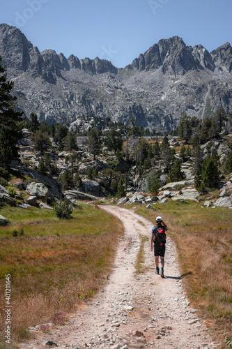 Senderista caminando por un camino en el parque nacional de aiguestortes con vis Fototapet