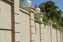 One Large Concrete Yellow Brown Fence Wall In Green Vegetation With White Round Lanterns Outside