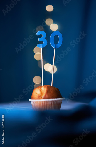 Birthday cupcake or muffin with number thirty (30) and lights on the blue background. Birthday or anniversary concept
