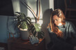 canvas print picture Beautiful young woman next to a trendy monstera plant with big leaves indoor with morning sun rays. Autumn concept.