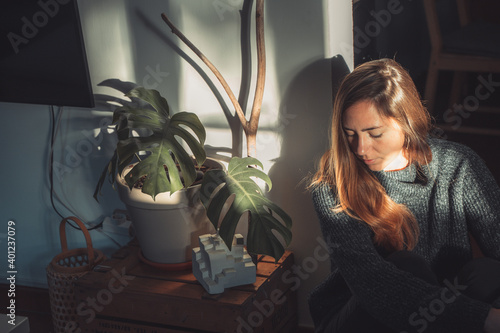 canvas print motiv - deliris : Beautiful young woman next to a trendy monstera plant with big leaves indoor with morning sun rays. Autumn concept.