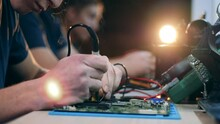 Male Engineer Is Soldering A Computer Circuit