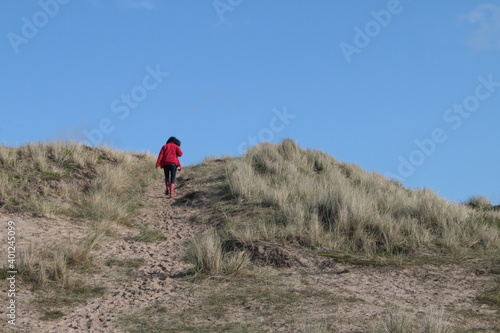 Canvastavla Beautiful coast landscape of sandy grass dunes with female lone figure in red co