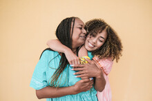 Cheerful African Mother And Adult Daughter Hugging Each Other While Wearing Traditional Dress