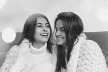 Laughting. Portrait Of Beautiful Brunette Women In Comfortable Soft Longsleeves On Studio Background, Black And White. Home Comfort, Emotions, Facial Expression, Winter Mood Concept. Friendship.