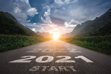 2021, The New Year 2021 or the beginning of the concept of the word 2021 is written on the road in the middle of the asphalt road with a sunset mountain backdrop, concepts of planning and challenges