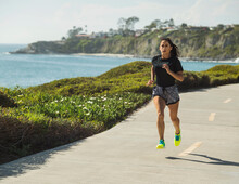 USA, California, Dana Point, Woman Running On Road By Coastline