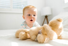Baby Boy (6-11 Months) Looking At Teddy Bear On Bed