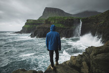 Denmark, Faroe Islands, Gasadalur Village, Mulafossur Waterfall, Man Standing On Cliff And Looking At Mulafossur Waterfall Falling Into Ocean