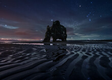 Picturesque View Of Starry Sky With Northern Lights Over Seashore With Huge Rock At Night In Iceland In Long Exposure
