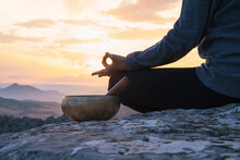 Low Angle Side View Of Tranquil Female Sitting In Padmasana Position Near Singing Bowl And Meditating While Relaxing In Mountains At Sunset Time