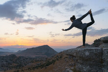 Low Angle Side View Of Flexible Female Standing In Lord Of The Dance Position Against Cloudy Sunset Sky While Practicing Yoga On Top Of Rocky Mountain