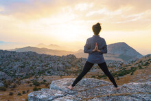 Full Body Back View Of Unrecognizable Barefoot Female Standing In Star Pose With Reverse Prayer Hands On Top Of Mountain While Practicing Yoga In Nature At Sunset Time