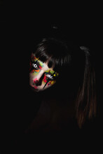 Creepy Female With Painted Face And In Contact Lenses Peeping Out Of Darkens At Night On Halloween