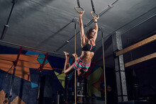 Determined Strong Young Sportswoman Doing Pull Ups On Gymnastic Rings During Intense Workout In Gym