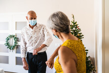Positive Mature Couple In Smart Casual Outfits And Face Masks Greeting By Bumping Elbows While Standing Near Decorated Shiny Christmas Tree