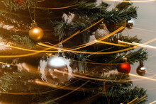 Detail Of Christmas Tree With Decorative Colorful Balls And Glowing Garland In Long Exposure